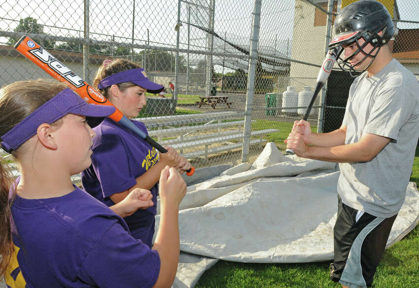 From left, Times Union reporter Pete Iorizzo gets some pointers from some players at the West Albany Little League fields in Albany, NY on July 30, 2009. The girls team was to be competing in a big regional tournament in Albany in their quest to play in Portland Oregon for the Little League Softball World Series. (Lori Van Buren / Times Union)