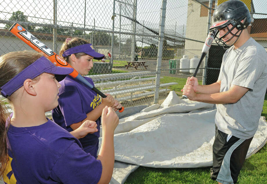 From left, Times Union reporter Pete Iorizzo gets some pointers from Jessica Ricciardi, left, age 12, of Colonie, and Kaylee Noll, age 13, of Colonie, at the West Albany Little League fields in Albany, NY on July 30, 2009.  The girls team will be competing in a big regional tournament in Albany and if the team wins they will be heading to Portland Oregon for the Little League Softball World Series. (Lori Van Buren / Times Union) Photo: LORI VAN BUREN / 00004941A