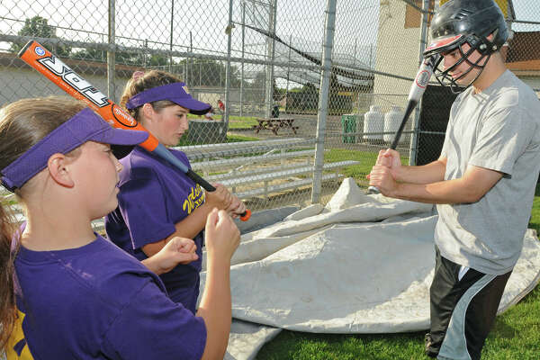 From left, Times Union reporter Pete Iorizzo gets some pointers from Jessica Ricciardi, left, age 12, of Colonie, and Kaylee Noll, age 13, of Colonie, at the West Albany Little League fields in Albany, NY on July 30, 2009.  The girls team will be competing in a big regional tournament in Albany and if the team wins they will be heading to Portland Oregon for the Little League Softball World Series. (Lori Van Buren / Times Union)
