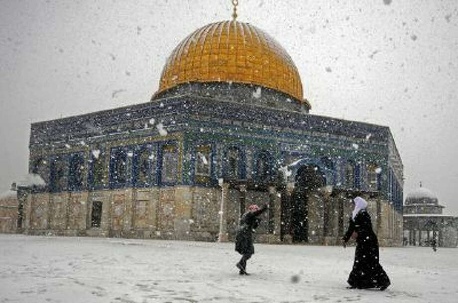 Two Palestinian women play with snow outside Al-Aqsa Mosque in Jerusalem, Thursday, Dec. 12, 2013.