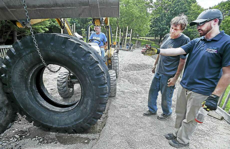 "Project Manager Jeff Weaver, uses a backhoe to move a giant tire into the area as Dan Ney, an electricianand mechanic Mark Kovaleski, all employees at Larry Janesky's Basement Systems, Inc. kick off a three-day build, constructing an 8,000 square foot handicap accessible playground at the Ansonia Nature & Recreation Centet Playground, Friday, July 15, 2016. Janesky's sister, Charlene Bieber said, ""The playground Includes towers linked together by bridges, a spiral tube slide, a bucket swing, tire swing, fire pole, rope climb and amphitheater seating for parents."" (Catherine Avalone/New Haven Register) Photo: Journal Register Co. / New Haven RegisterThe Middletown Press"