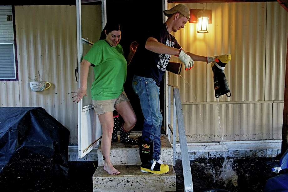 Shelley DeCarlo, 40, left, and Daniel Stover, 17, empty their boots of water as they enter the home of Laura Albritton to help her save some personal belongings from flood water in Sorrento, La., Saturday, Aug. 20, 2016.  Louisiana continues to dig itself out from devastating floods, with search parties going door to door looking for survivors or bodies trapped by flooding. (AP Photo/Max Becherer) Photo: AP / FR171354 AP