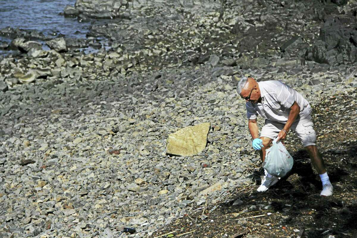 Paul Maccio picks up trash along the East Shore in New Haven to help contribute to the cleanliness of the area and keep garbage from entering the Sound. (Anna Bisaro - New Haven Register)