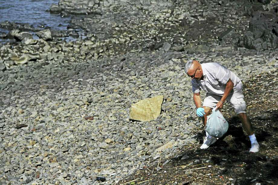 Paul Maccio picks up trash along the East Shore in New Haven to help contribute to the cleanliness of the area and keep garbage from entering the Sound. (Anna Bisaro - New Haven Register) Photo: Journal Register Co.