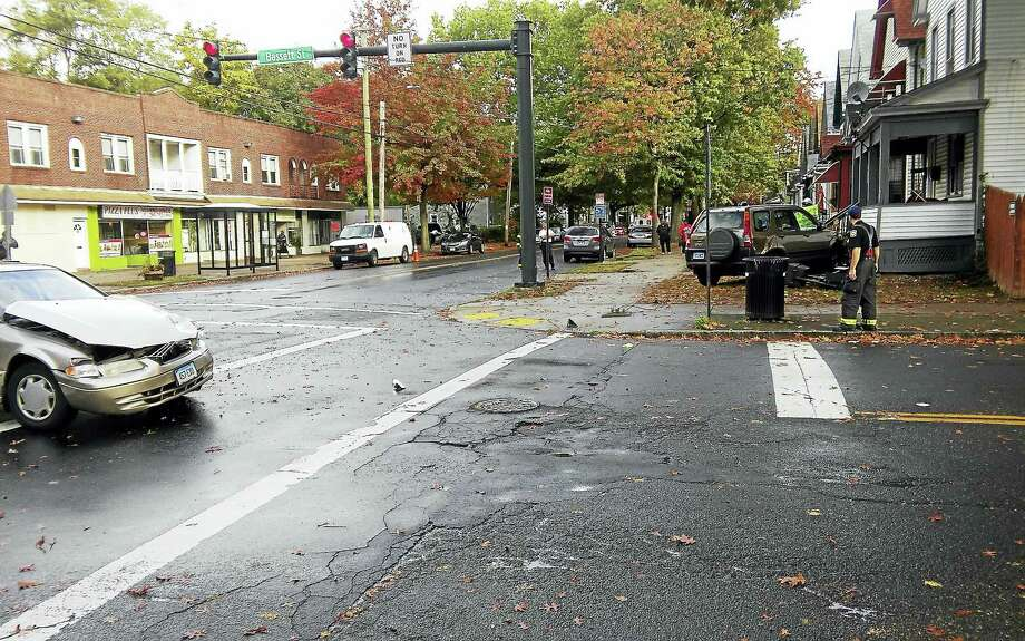 (Photo by Joe Tomaso)  The intersection of Shelton Avenue and Bassett Street was shut down for about an hour Friday after a car hit an SUV, which then hit a house. Photo: Digital First Media
