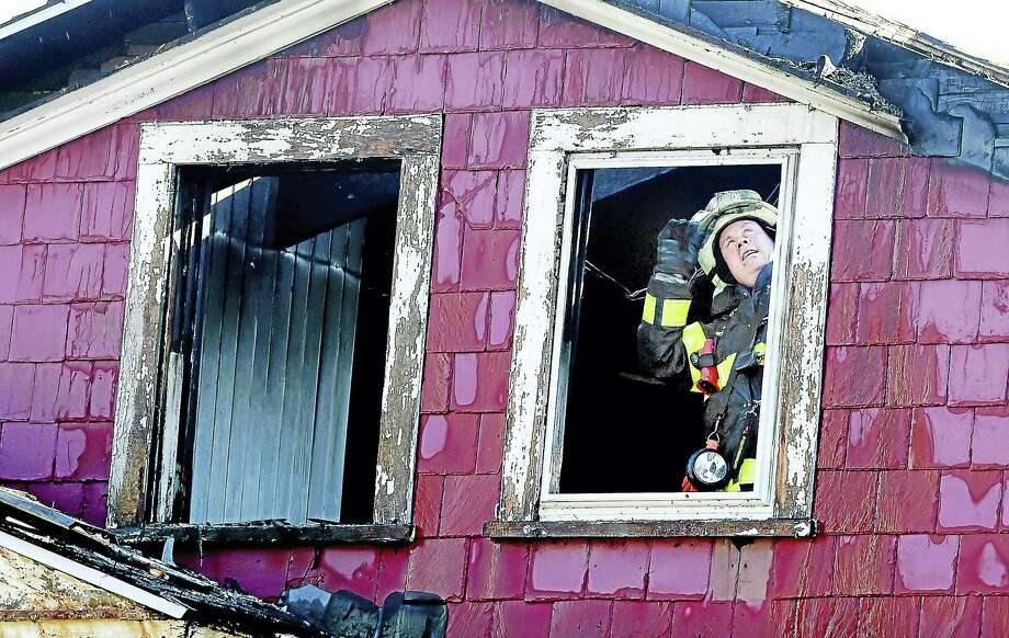 (Arnold Gold-New Haven Register)  New Haven Fire Department Battalion Chief William Gould peers up at the roof in the back of 1187 Chapel St. in New Haven after a fire was under control on 10/18/2016. Photo: Digital First Media