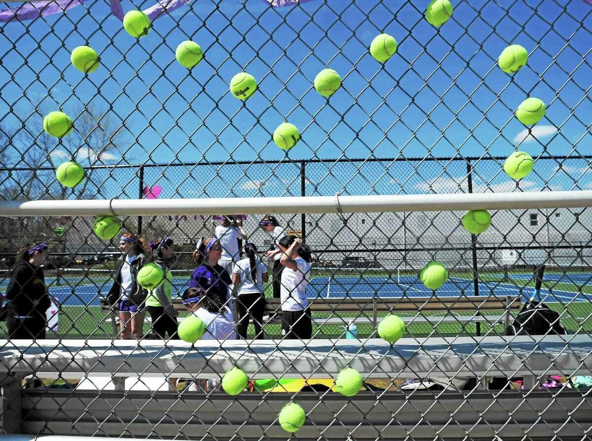 (Peter Hvizdak - New Haven Register) The Law High School Girls' tennis team uses tennis balls to make a heart memorial in honor of Maren Sanchez Monday, April 28, 2014 at the school's tennis court.