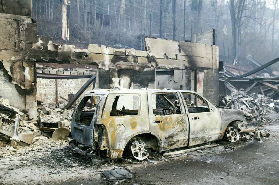 A scorched vehicle sits next to a burned out building in Gatlinburg, Tenn., on Tuesday, Nov. 29, 2016. The fatal fires swept over the tourist town the night before, causing widespread damage. (AP Photo/Erik Schelzig) Photo: AP / Copyright 2016 The Associated Press. All rights reserved.