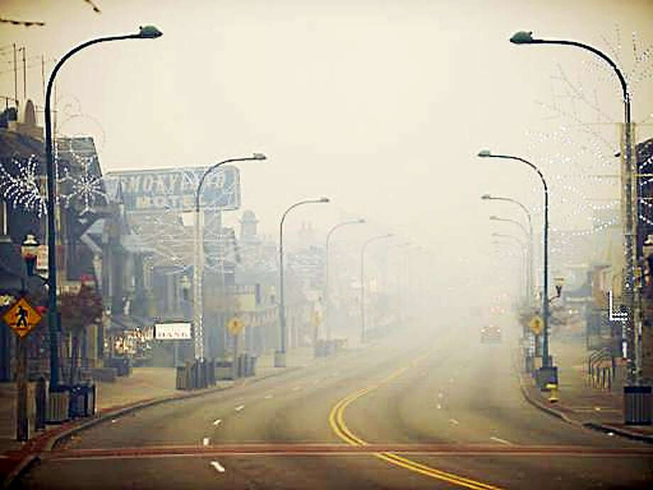 Thick smoke from area forest fires looms in Gatlinburg, Tenn., Monday, Nov. 28, 2016. Gatlinburg officials say several areas are being evacuated as a result of fires in and around Great Smoky Mountains National Park. (Brianna Paciorka/Knoxville News Sentinel via AP) Photo: AP / copyright ? 2016