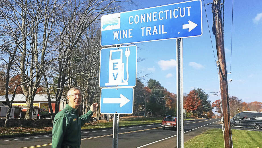 (Wes Duplantier/The New Haven Register) Keith Bishop, co-owner of Bishop's Orchards, stands next to a blue sign indicating an electric vehicle charging station (left) is visible near the front entrance of the farm store's parking lot on the Boston Post Road in Guilford. That charging station will be part of an alternative fuels corridor along Interstate 95 in the New Haven area. Photo: Digital First Media