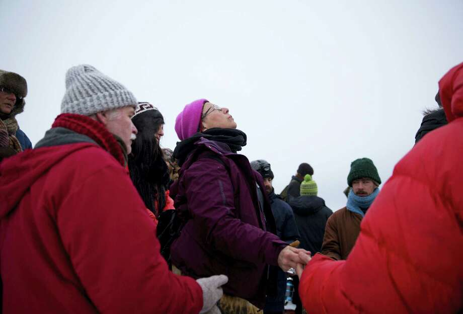 In this Thursday, Dec. 1, 2016 photo, Elena Ruben Goodman, of Oakland, Calif., waits her turn to pray by the Cannonball river during a Native American water ceremony at the Oceti Sakowin camp where people have gathered to protest the Dakota Access oil pipeline in Cannon Ball, N.D. On Thursday, the camp near the confluence of the Missouri and Cannonball rivers was shrouded in snow, much of it compacted by foot and vehicle traffic. Next week's forecast calls for single digits and subzero wind chills. (AP Photo/David Goldman) Photo: AP / Copyright 2016 The Associated Press. All rights reserved.