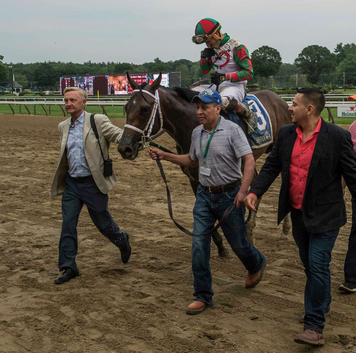 Trainer Jason Servis, left leads Firenze Fire with jockey Irad Ortiz Jr. to the winner's circle after winning 103rd running of The Sanford Saturday July 23, 2017 at the Saratoga Race Course in Springs, N.Y. (Skip Dickstein/Times Union)