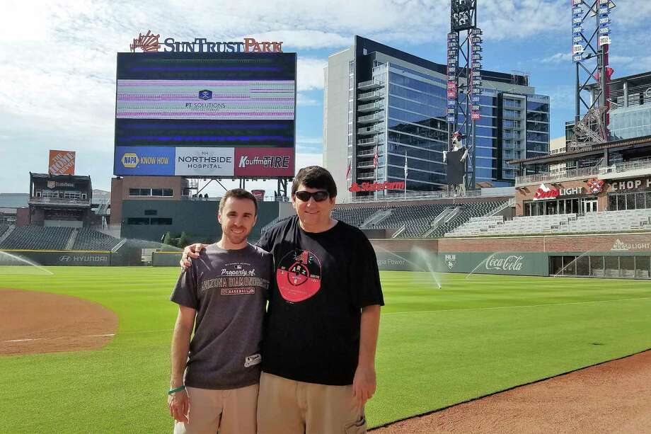 In this 2017 photo provided by Frank Gennario Jr., Frank Gennario Jr. and his son, Tony, pose at SunTrust Park in Atlanta.  Frank Gennario lost his father to bone cancer when he was 16, and he clings tightly to memories of their days at Yankee Stadium. When Frank's only son was nearing the same age, it became critical to him that they build those same ballpark memories. So the pair set a goal: see their beloved Arizona Diamondbacks play in every big league park. Ten years later, they have completed their quest. (Frank Gennario Jr. via AP) ORG XMIT: NY152 / Frank Gennario Jr.