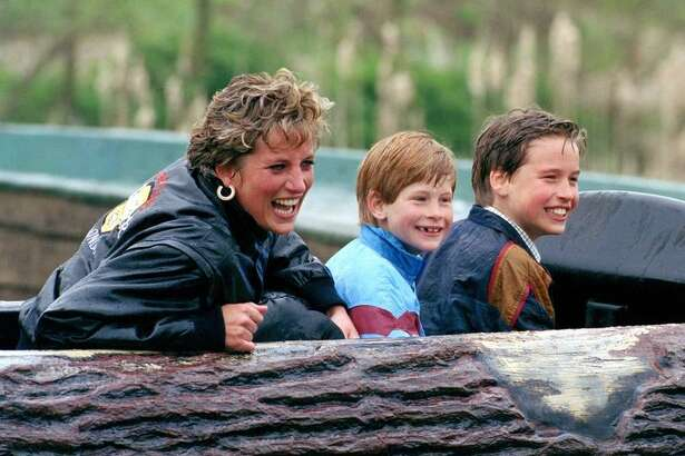 Princess Diana enjoys a theme park ride with sons Harry (also at right) and William.