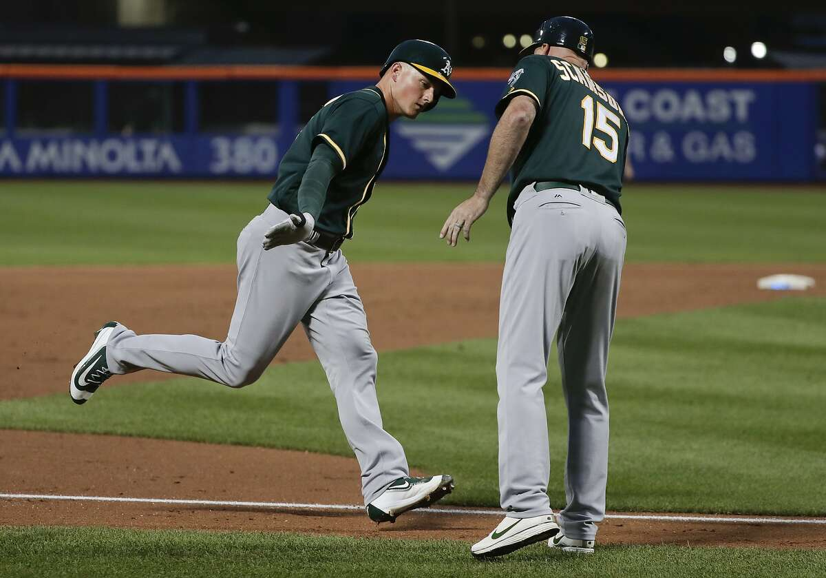 Oakland Athletics' Matt Chapman, left, is congratulated by acting third base coach Steve Scarsone (15) as he rounds the bases after hitting a solo home run against the New York Mets during the third inning of a baseball game, Saturday, July 22, 2017, in New York. (AP Photo/Julie Jacobson)