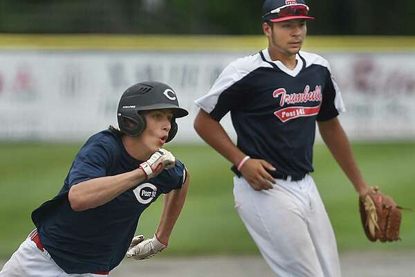 Trumbull third baseman Jake Texeria keeps watch on home as Cheshire's Eli Battipaglia rounds third to score on a single by Ryan Strollo in the southern regional playoffs of the American Legion tournament, Saturday, July 22, 2017, at Palmer Field in Middletown. Cheshire won, 1-0. (Catherine Avalone – Hearst Connecticut Media)
