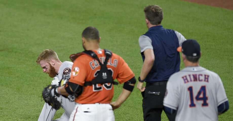 A trainer and Houston Astros manager A.J. Hinch (14) run to the aid of Astros' Colin Moran, left, as Moran sits on the ground after he was injured during his at-bat in the sixth inning of a baseball game as Baltimore Orioles catcher Welington Castillo (29) looks on, Saturday, July 22, 2017, in Baltimore. (AP Photo/Nick Wass) Photo: Nick Wass/Associated Press