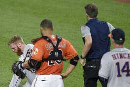 A trainer and Houston Astros manager A.J. Hinch (14) run to the aid of Astros' Colin Moran, left, as Moran sits on the ground after he was injured during his at-bat in the sixth inning of a baseball game as Baltimore Orioles catcher Welington Castillo (29) looks on, Saturday, July 22, 2017, in Baltimore. (AP Photo/Nick Wass)