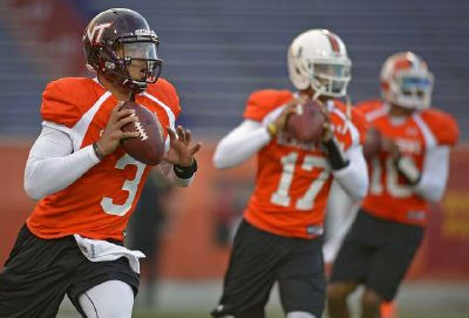 North Squad quarterback Logan Thomas of Virginia Tech (3) drops back with fellow quarterbacks Stephen Morris of Miami (17), middle, and Tajh Boyd of Clemson (10), right, during Senior Bowl practice.