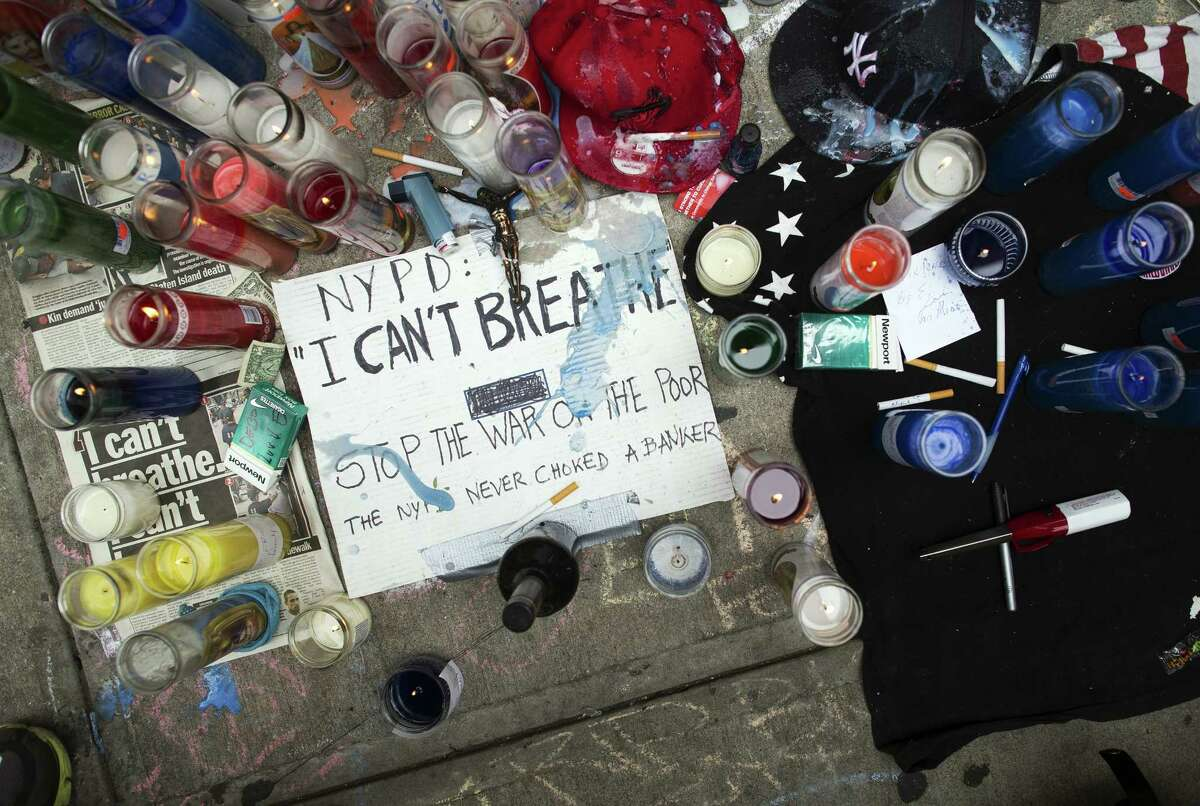 FILE - This July 19, 2014 file photo shows a memorial for Eric Garner on the pavement near the site of his death when taken into custody by police, in the Staten Island borough of New York. Three years after Garner's chokehold death the wheels of justice are turning more slowly than in similar cases. Federal prosecutors have said privately that a decision about whether to charge the police officer seen on video wrapping his arm around Garner's neck is still months away, frustrating the victim's family and leaving the officer's career in limbo. (AP Photo/John Minchillo, File) ORG XMIT: NYR301