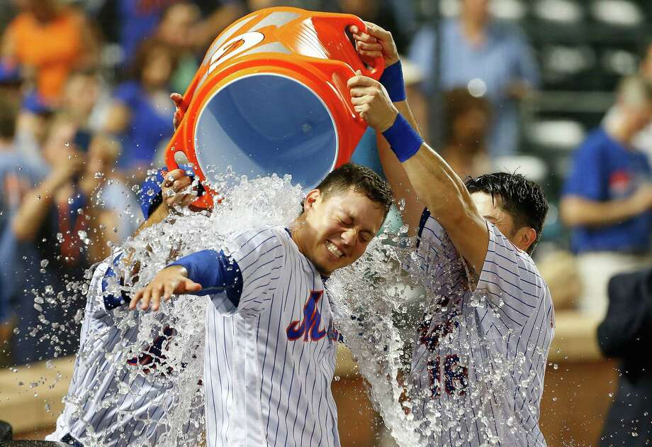 NEW YORK, NY - JULY 22:  Wilmer Flores #4 of the New York Mets is doused with water by teammates T.J. Rivera #54 and Travis d'Arnaud #18 after his ninth inning game winning home run against the Oakland Athletics at Citi Field on July 22, 2017 in the Flushing neighborhood of the Queens borough of New York City.  (Photo by Jim McIsaac/Getty Images) ORG XMIT: 700011714 Photo: Jim McIsaac / 2017 Getty Images