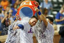 NEW YORK, NY - JULY 22:  Wilmer Flores #4 of the New York Mets is doused with water by teammates T.J. Rivera #54 and Travis d'Arnaud #18 after his ninth inning game winning home run against the Oakland Athletics at Citi Field on July 22, 2017 in the Flushing neighborhood of the Queens borough of New York City.  (Photo by Jim McIsaac/Getty Images) ORG XMIT: 700011714