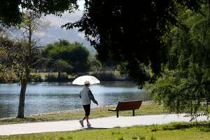 A woman strolls around Lake Elizabeth at Central Park in Fremont, Calif. on Thursday, July 20, 2017. Consistently rated as one of the safest cities in the nation, Fremont has not had any homicides reported since 2015.