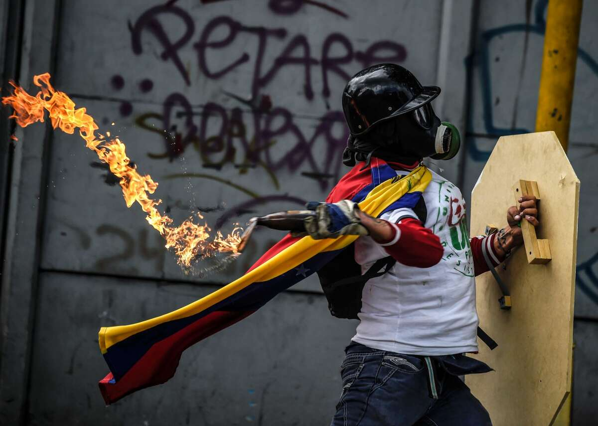 An opposition activist clashes with the police during a march towards the Supreme Court of Justice (TSJ) in an offensive against President Maduro and his call for Constituent Assembly in Caracas on July 22, 2017. The Legislative power, controlled by the opposition, appointed Friday a parallel supreme court in a public session claiming the TSJ judges had been illegally appointed by the parliaments former pro-government majority.