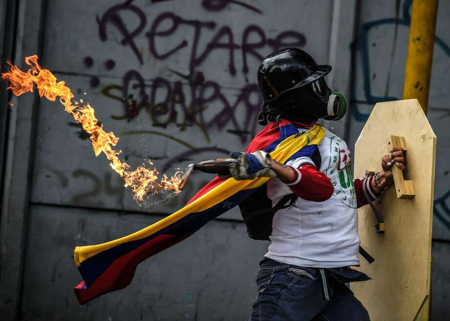 An opposition activist clashes with the police during a march towards the Supreme Court of Justice (TSJ) in an offensive against President Maduro and his call for Constituent Assembly in Caracas on July 22, 2017. The Legislative power, controlled by the opposition, appointed Friday a parallel supreme court in a public session claiming the TSJ judges had been illegally appointed by the parliaments former pro-government majority.  Photo: JUAN BARRETO/AFP/Getty Images