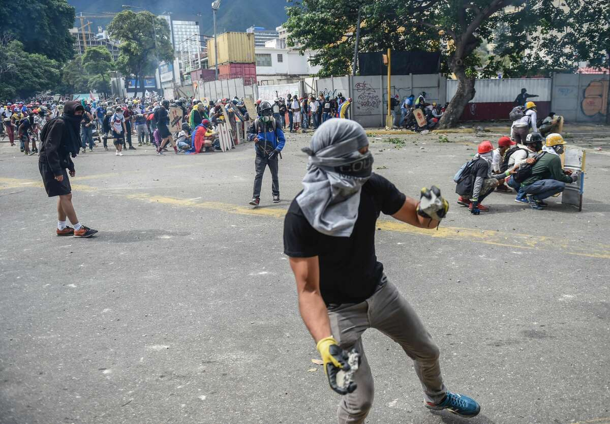 Opposition activists clash with riot police during a march towards the Supreme Court of Justice (TSJ) in an offensive against President Maduro and his call for Constituent Assembly in Caracas on July 22, 2017. The Legislative power, controlled by the opposition, appointed Friday a parallel supreme court in a public session claiming the TSJ judges had been illegally appointed by the parliaments former pro-government majority.