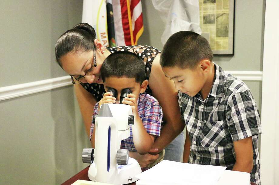 Erika Villalobos looks over the shoulder of Andre Villanueva as he peers into the microscope to see a moth up close. His brother Erik looks on. The family drove out to the event because the boys have shown a lot of interest in insects. Photo: David Taylor