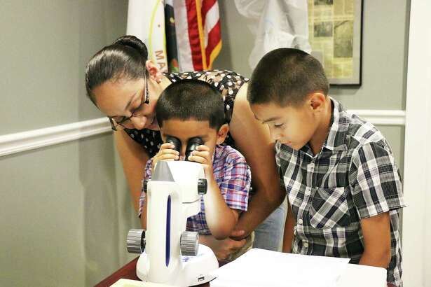 Erika Villalobos looks over the shoulder of Andre Villanueva as he peers into the microscope to see a moth up close. His brother Erik looks on. The family drove out to the event because the boys have shown a lot of interest in insects.