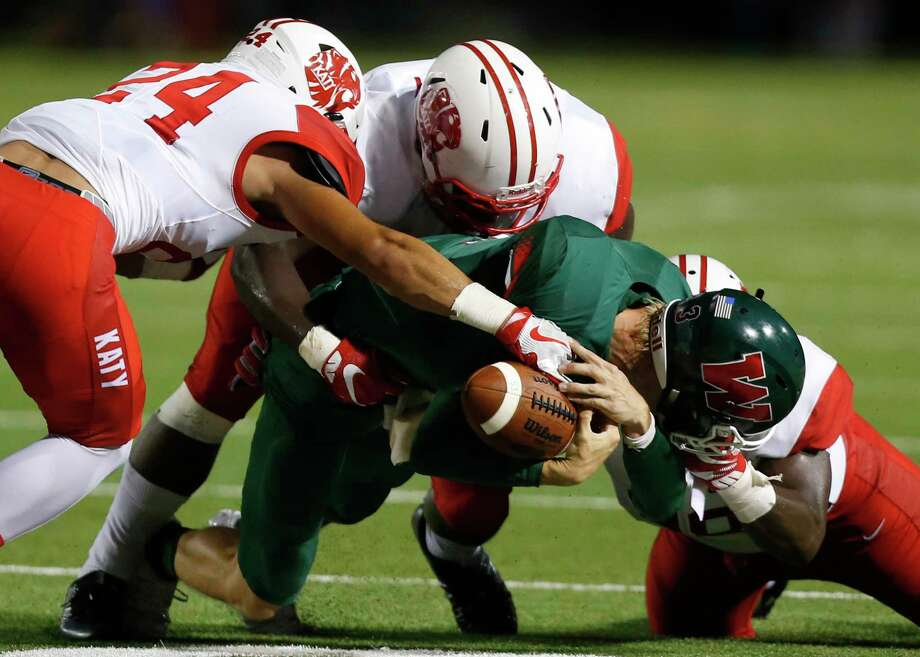 The Woodlands quarterback Eric Schmid loses the handle on the football as he is hit in the backfield by Katy's Matt Kissamis (24), Corey Bethley and Michael Matus during the first quarter of a non-district high school football game at Woodforest Stadium on Friday, Sept. 9, 2016, in The Woodlands. ( Brett Coomer / Houston Chronicle ) Photo: Brett Coomer, Staff / © 2016 Houston Chronicle