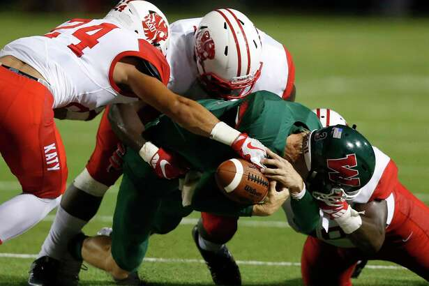 The Woodlands quarterback Eric Schmid loses the handle on the football as he is hit in the backfield by Katy's Matt Kissamis (24), Corey Bethley and Michael Matus during the first quarter of a non-district high school football game at Woodforest Stadium on Friday, Sept. 9, 2016, in The Woodlands. ( Brett Coomer / Houston Chronicle )