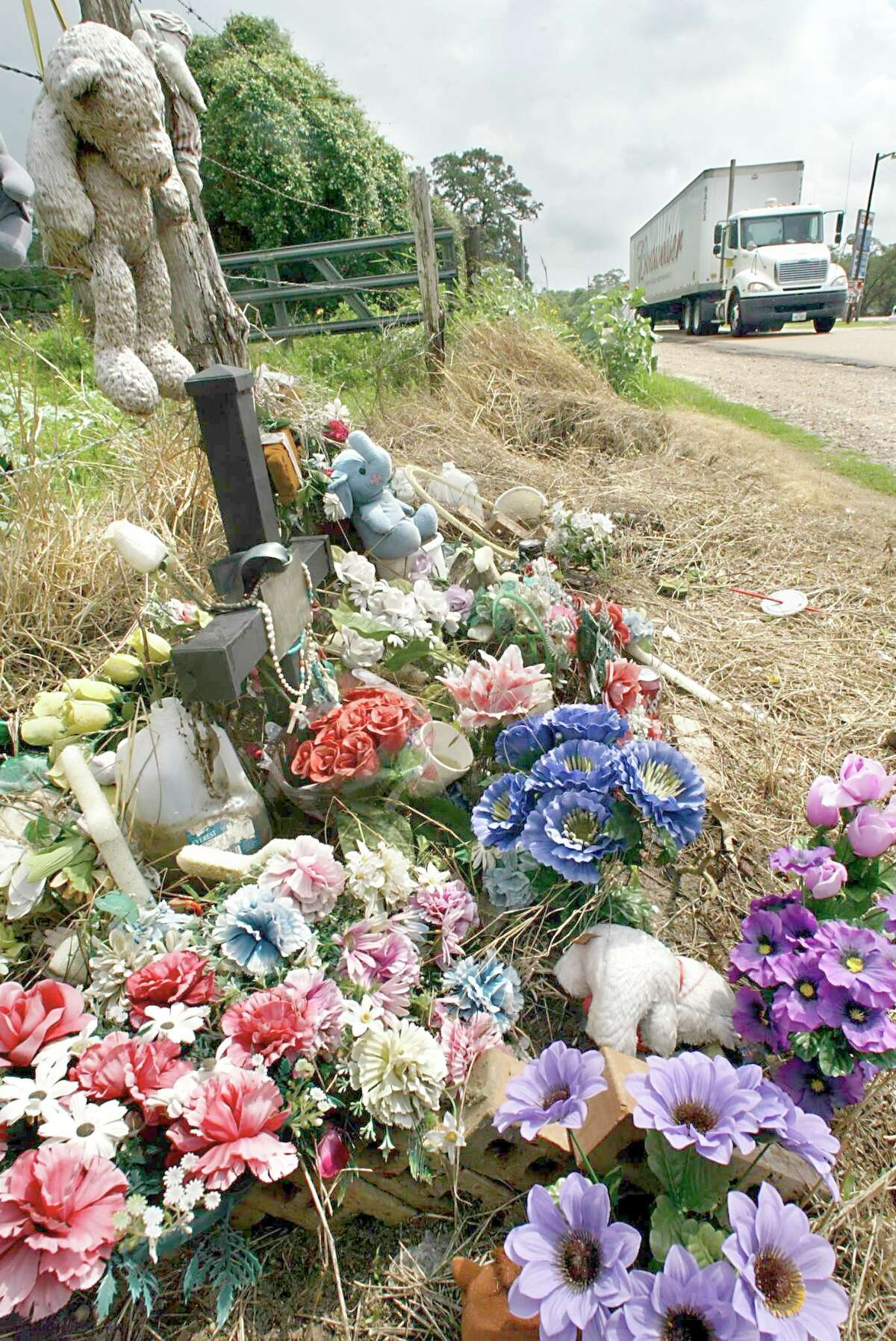Flowers, stuffed teddy bears, water and rosary beads are just some of items left a year later at the site where 19 illegal immigrants were found dead in Victoria.