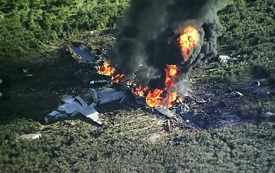 In this July 10, 2017 frame from video, smoke and flames rise from a military plane that crashed in a farm field, in Itta Bena, Miss., killing several. (WLBT-TV via AP) Photo: AP / WLBT-TV