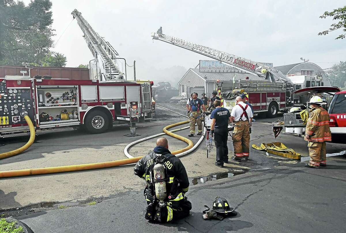 Milford firefighters battle a large fire Tuesday at Milford Auto Recycling at 70 S. Washington St. in Milford.