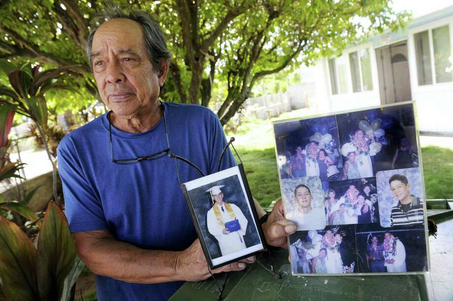 """In this Monday, July 10, 2017 photo, Clifford Kang, father of soldier Ikaika E. Kang, poses with photo of his son in Kailua, Hawaii.  Ikaika E. Kang, an active-duty U.S. soldier, was arrested over the weekend on terrorism charges that accuse him of pledging allegiance to the Islamic State group and saying he wanted to """"kill a bunch of people."""" Photo: Bruce Asato / The Star-Advertiser Via AP   / The Star-Advertiser"""