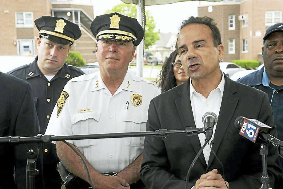 Bridgeport Mayor Joe Ganim,  with Police Chief Armando ?A.J.? Perez, speaks at a press conference at the Charles F. Greene Homes in Bridgeport June 16. Photo: Ned Gerard / Hearst Connecticut Media