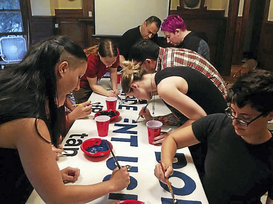 """(Brian Zahn/Hearst Connecticut Media) IV Staklo, left, leads the painting of a banner reading """"Millionaires Don't Represent Us."""" Photo: Digital First Media"""