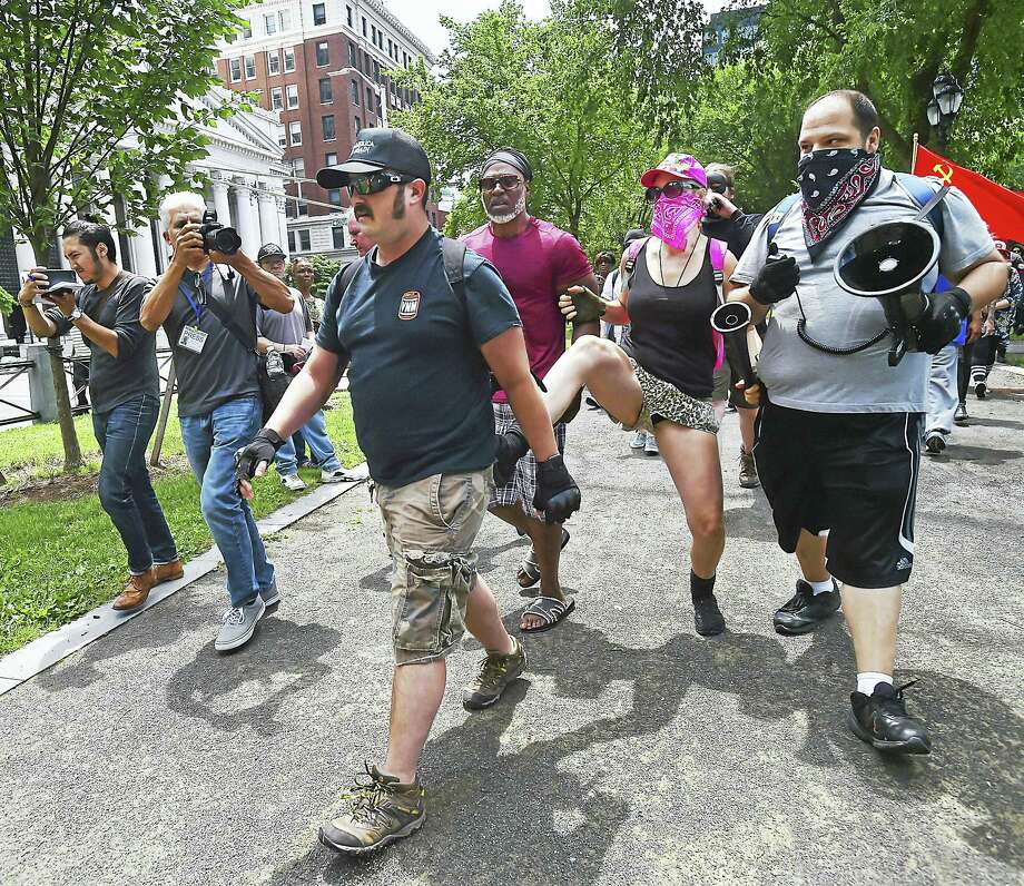 "One man wearing a black hat with ""Make America Great Again,"" is kicked by a counter protester at a rally, Saturday, July 8, 2017, at the New Haven Green. Photo: Catherine Avalone / Hearst Connecticut Media   / Catherine Avalone/New Haven Register"
