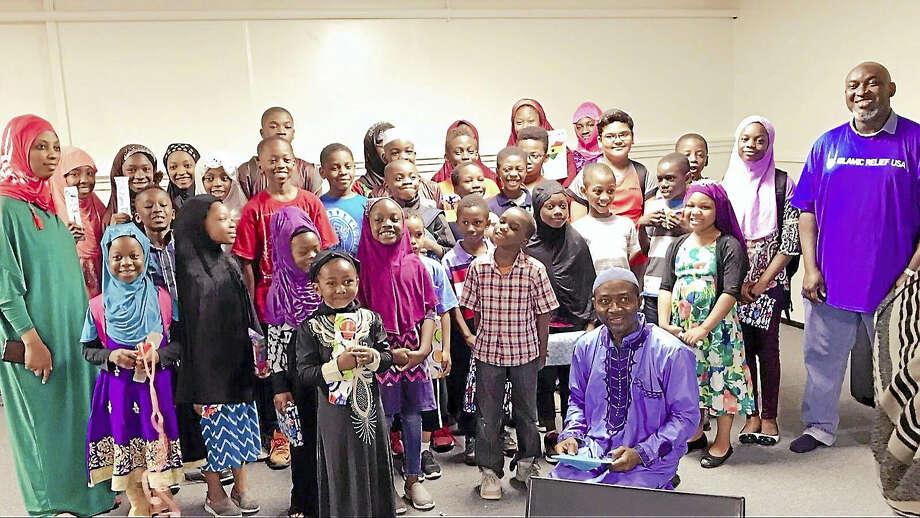 Contributed photo   The children of BAQIS Fellowship, Inc. pose with their toys. Their teacher, BAQIS President Mohamed Turay is sitting. Far right is Islamic Relief USA volunteer and MHSI board member who delivered the toys. Photo: Digital First Media