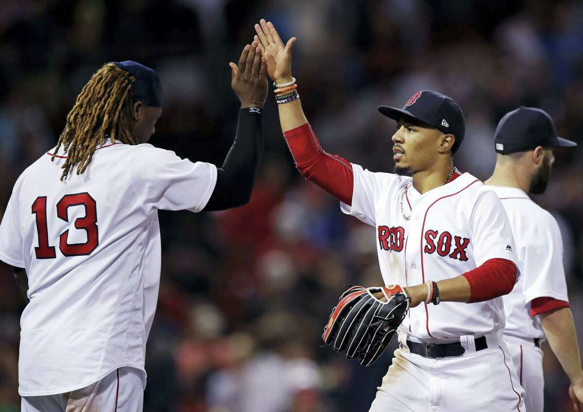 Mookie Betts, right, is congratulated by Hanley Ramirez after Boston's win over the Twins on Thursday night.