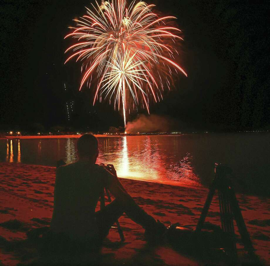 Milford resident Steven Cugini shoots stills and videos of the West Haven fireworks using a tripod on Gull Beach last year. Photo: Catherine Avalone / Hearst Connecticut Media   / New Haven RegisterThe Middletown Press