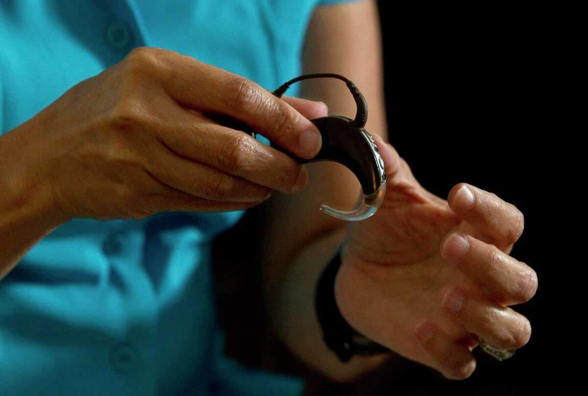Susan Langlois shows her cochlear implant, a surgically implanted medical device that sends sounds signals to the brain, during an interview at her home Wednesday, July 5, 2017, in Spring.