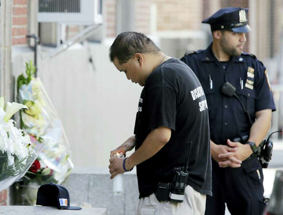 A man lights and leaves a candle at the entrance to the 46th Precinct in the Bronx borough of New York, Wednesday, July 5, 2017. A police officer from the 46th Precinct was shot to death early Wednesday, ambushed inside her command post RV by an ex-convict who once ranted online about his treatment in prison and about police getting away with killing people, authorities said. He was later killed after pulling a gun on police. Photo: AP Photo/Seth Wenig    / Copyright 2017 The Associated Press. All rights reserved.