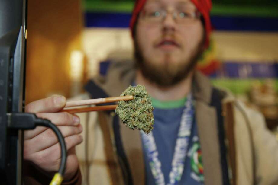 David Zalubowski/ the associated   Sales associate Matt Hart uses a pair of chopsticks to hold a bud of Lemon Skunk, the strain of highest potency available at the 3D Dispensary, in Denver. Photo: AP / AP