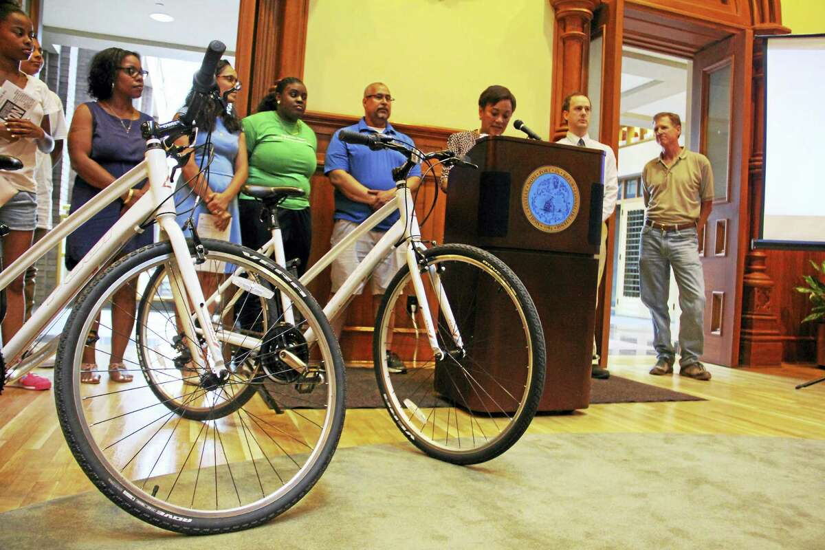 Bikes used by the Youth Conservation Corps members placed near Mayor Toni Harp during a press conference on the city's sustainability efforts Wednesday at City Hall.