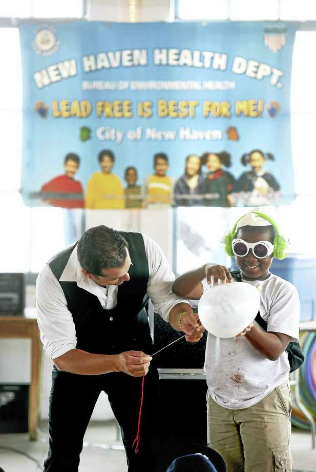 In this file photo, magician Elac Aviles (left) of Waterbury gets assistance from a child with putting a needle through a balloon during the Lead Awareness Picnic at Lighthouse Point Park in New Haven in 2016. Photo: Arnold Gold — New Haven Register
