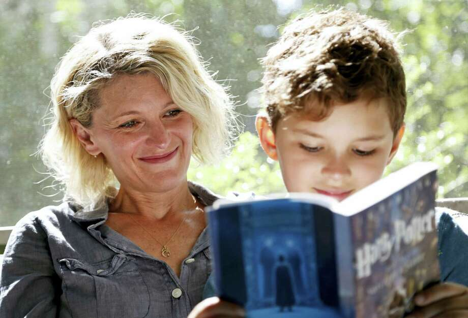 "Theo Galkin, 8, rereads a favorite part of ""Harry Potter and the Sorcerer's Stone"" while posing for a picture with his mother Chloe Galkin at their home in South Orange, N.J., Wednesday, June 28, 2017. As the 20th anniversary of the initial publishing of the first Harry Potter book is celebrated this week, another generation is being introduced to Harry, Hogwarts and all the rest of the magical world created by author J.K. Rowling. Photo: Seth Wenig / AP Photo   / Copyright 2017 The Associated Press. All rights reserved."